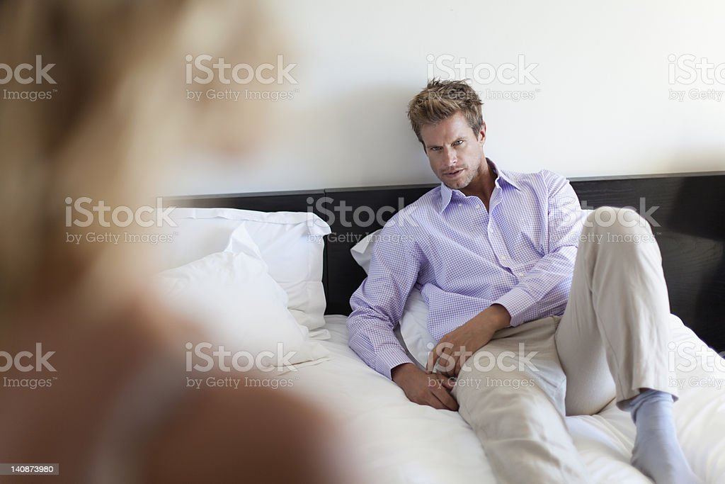 Man laying on bed looking at girlfriend stock photo