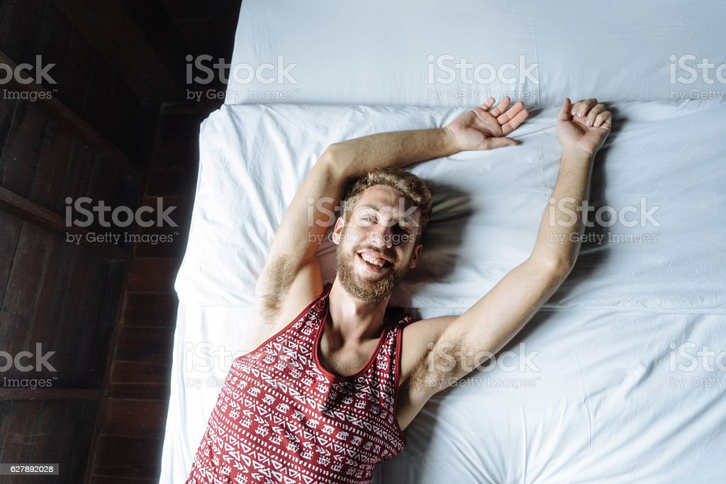 Man laying on bed stock photo