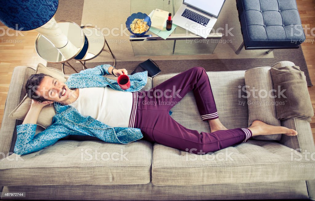 Man laying on couch stock photo