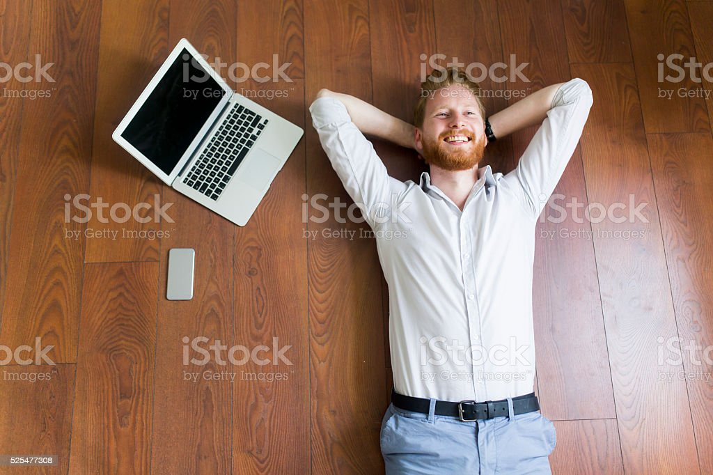 Man laying on the floor by the laptop stock photo