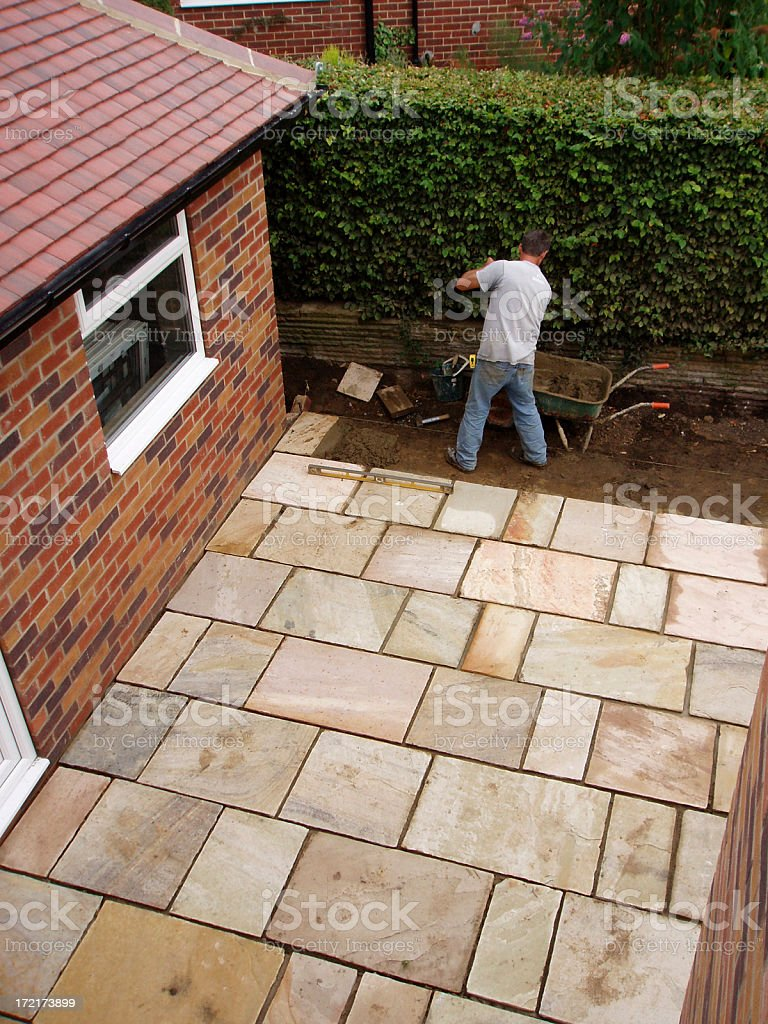 man laying patio paving slabs in house garden royalty-free stock photo
