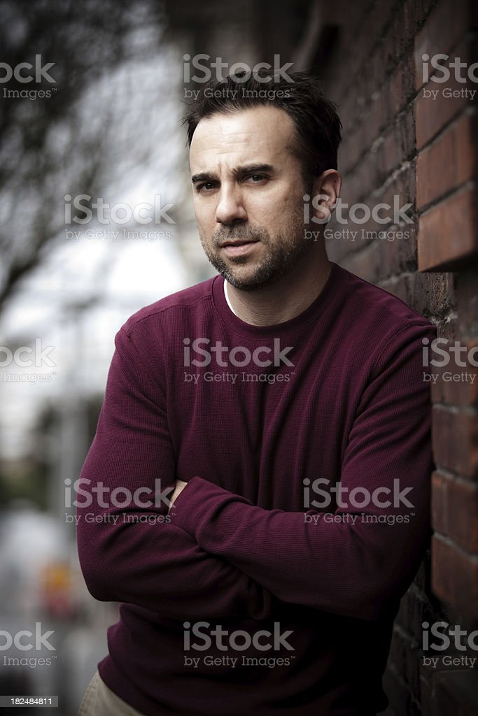 Man Leaning Against a Brick Wall royalty-free stock photo