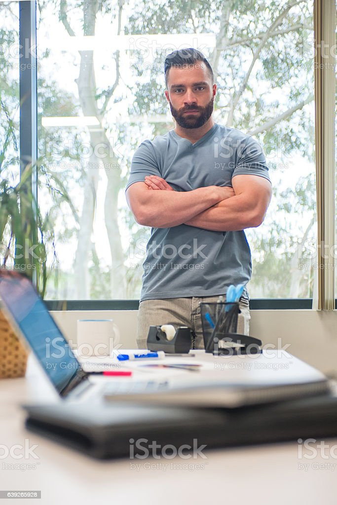 Man Leaning Against Office WIndow With His Arms Crossed stock photo