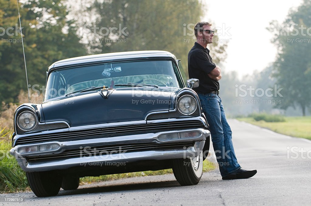 Man leaning against retro car on a back road royalty-free stock photo