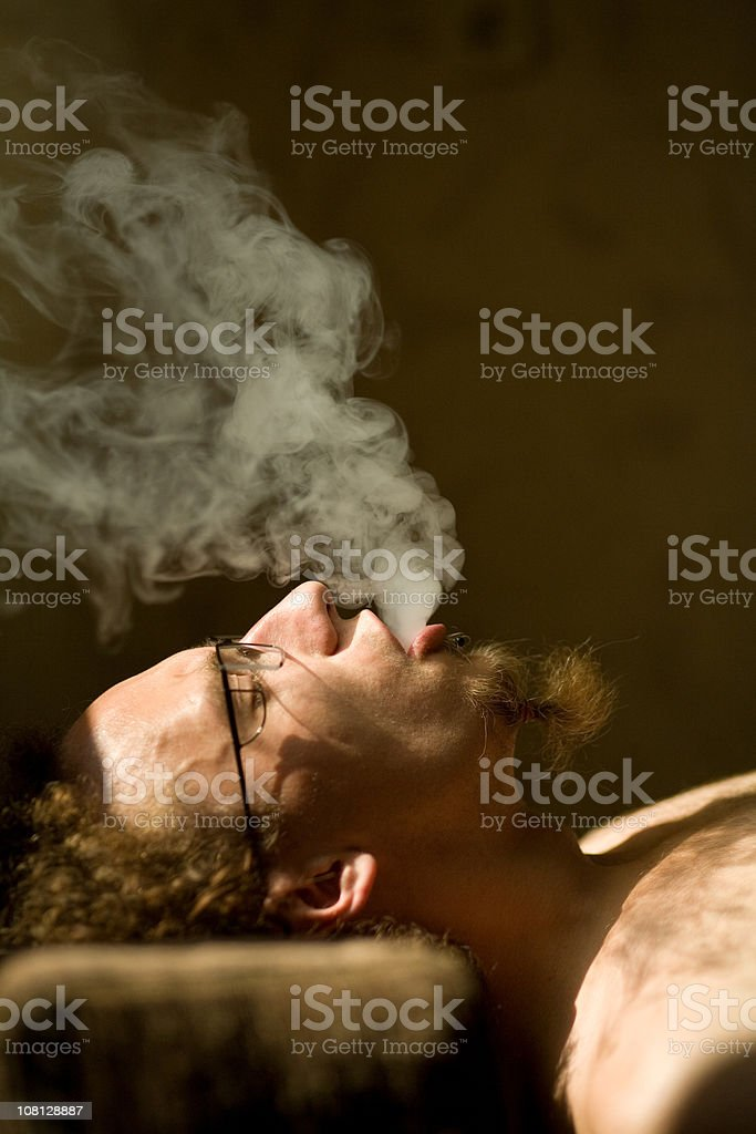 Man Leaning Back and Exhaling Smoke royalty-free stock photo