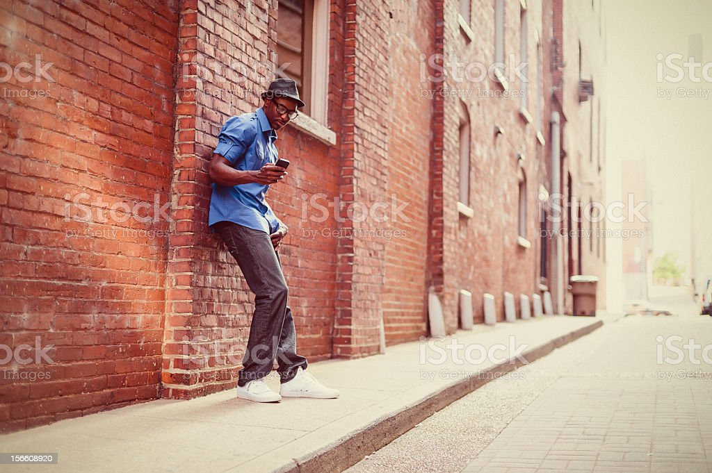 A man leaning on a red brick wall to send a text message royalty-free stock photo