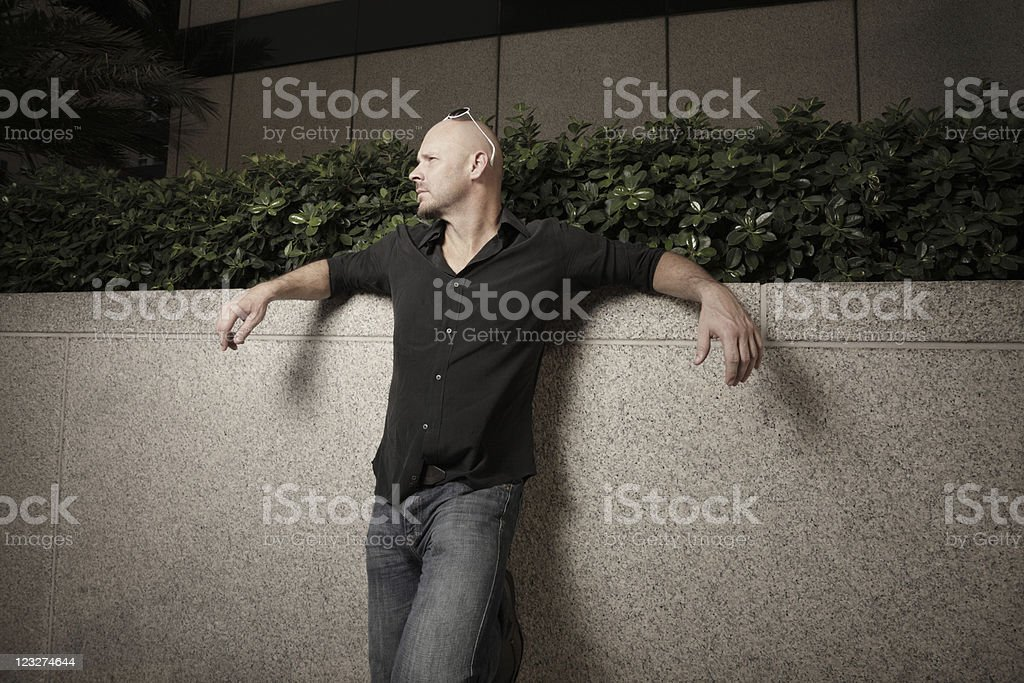 Man leaning on a wall stock photo