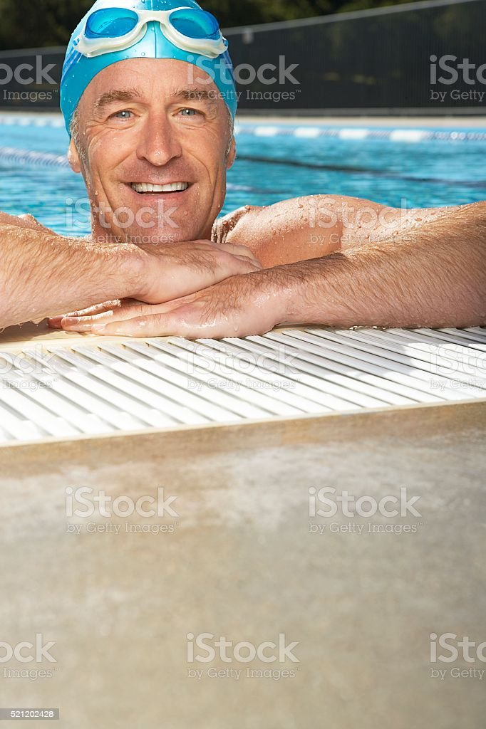 Man leaning on edge of swimming pool stock photo