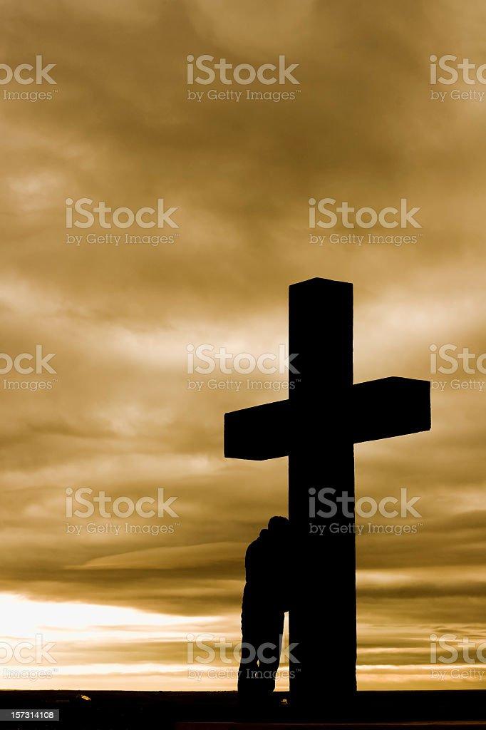 Man leaning on huge cross in despair against cloudy skies royalty-free stock photo