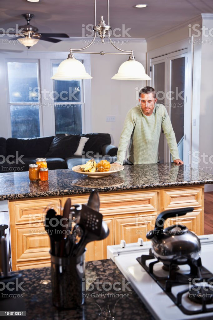 Man leaning on kitchen counter stock photo