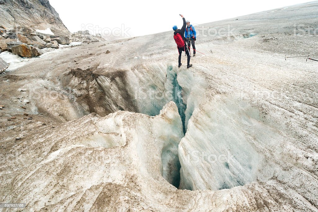 Man leans back to photograph glacier crevasse stock photo