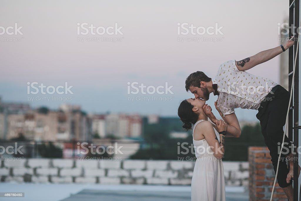 Man leans out of window to kiss woman in cityscape stock photo