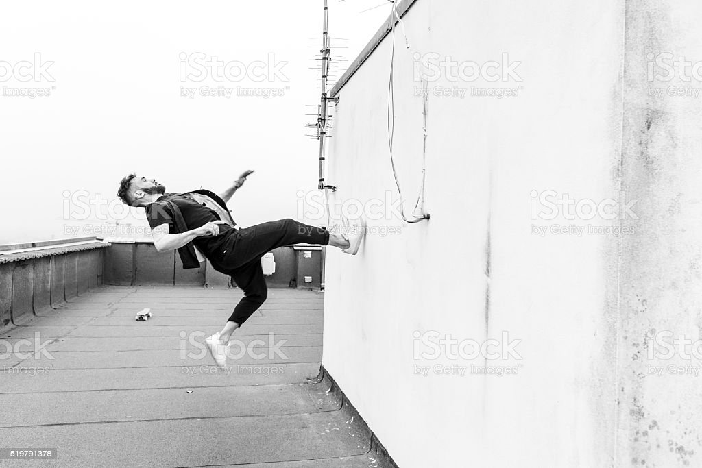 man leaping against a wall stock photo