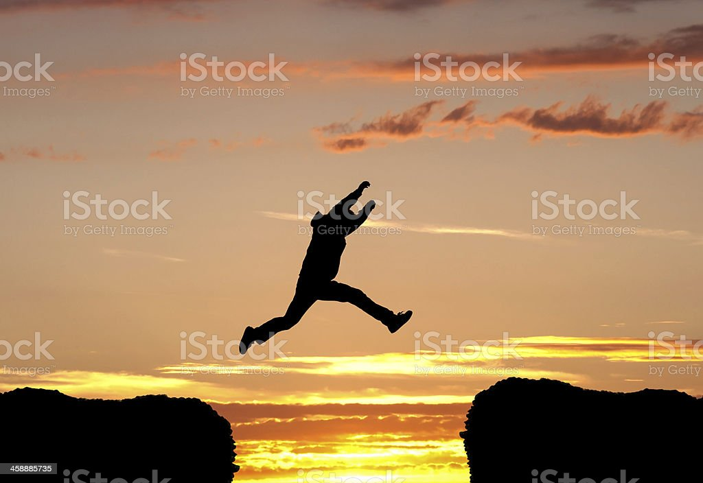Man leaping into the sunset stock photo