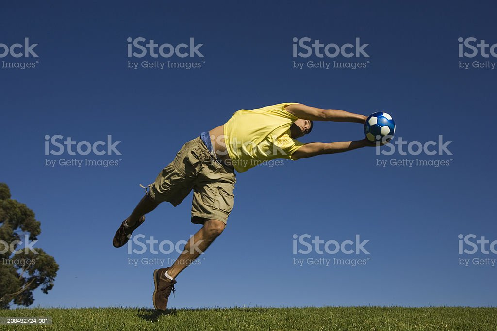 Man leaping to catch soccer ball royalty-free stock photo