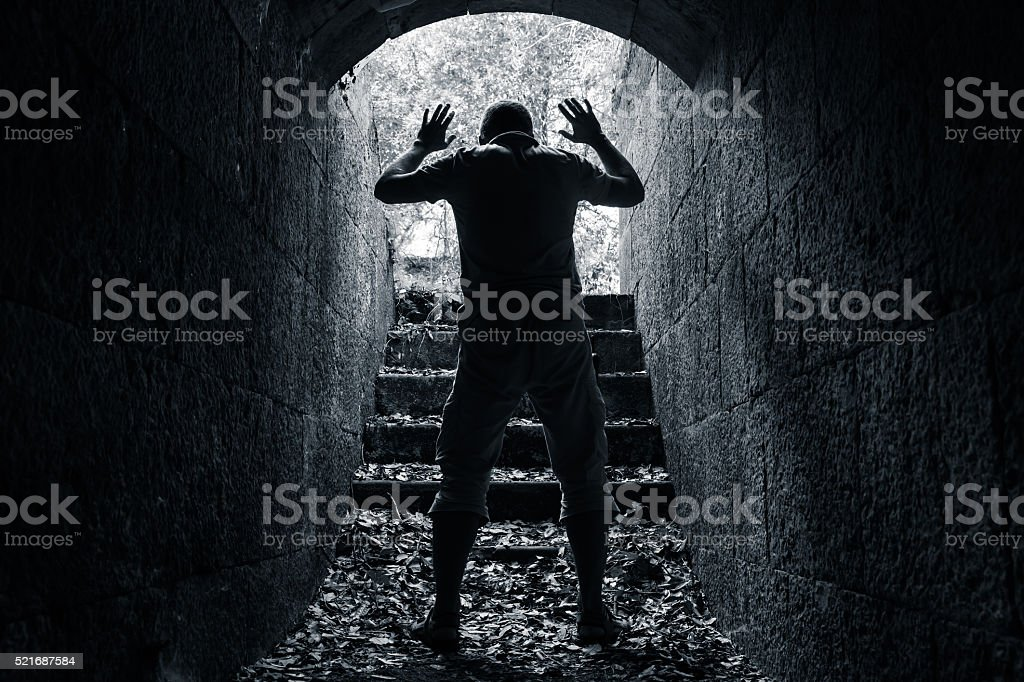 Man leaves dark stone tunnel with raised hands stock photo