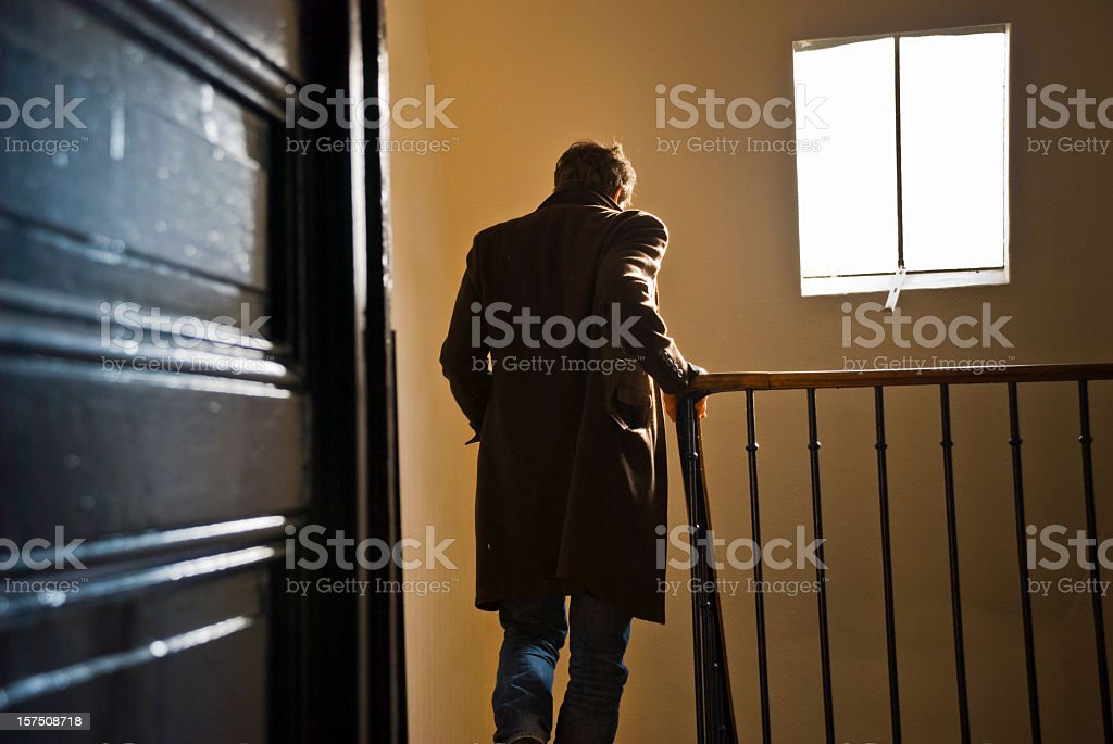 Man leaves home and goes downstairs  stock photo