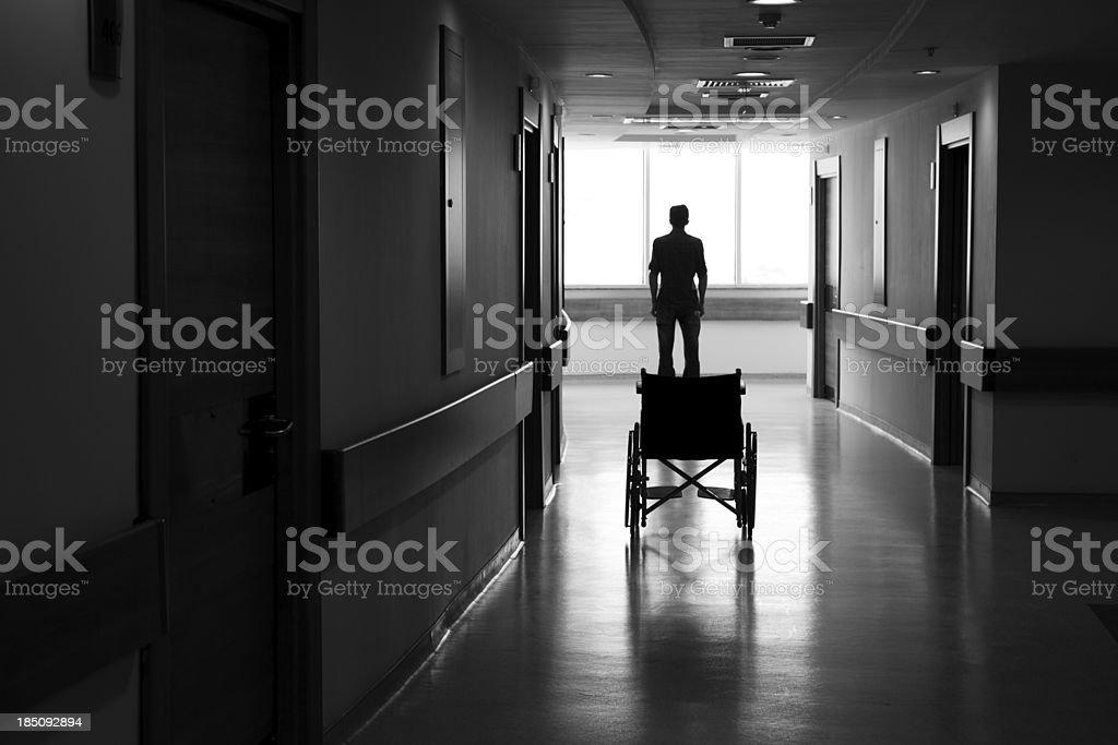 Man leaving wheelchair in corridor of hospital royalty-free stock photo