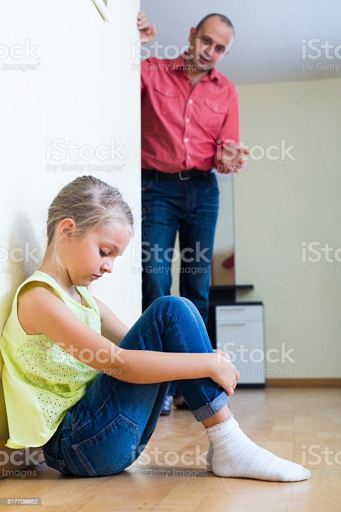 Man lecturing unpleased little girl stock photo