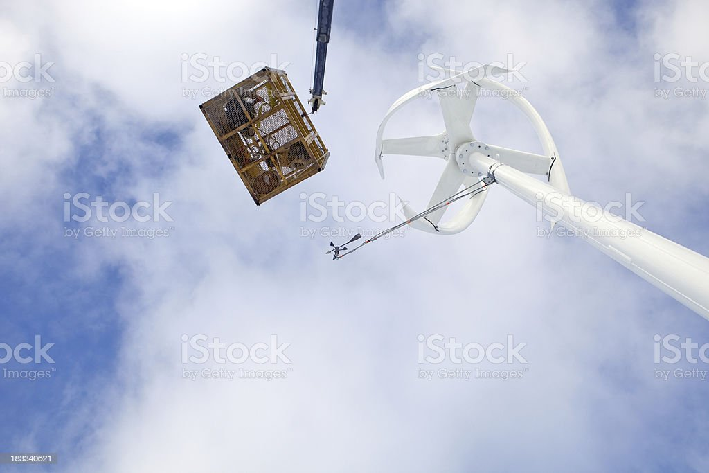 Man Lift Basket over a Vertical Axis Wind Turbine stock photo