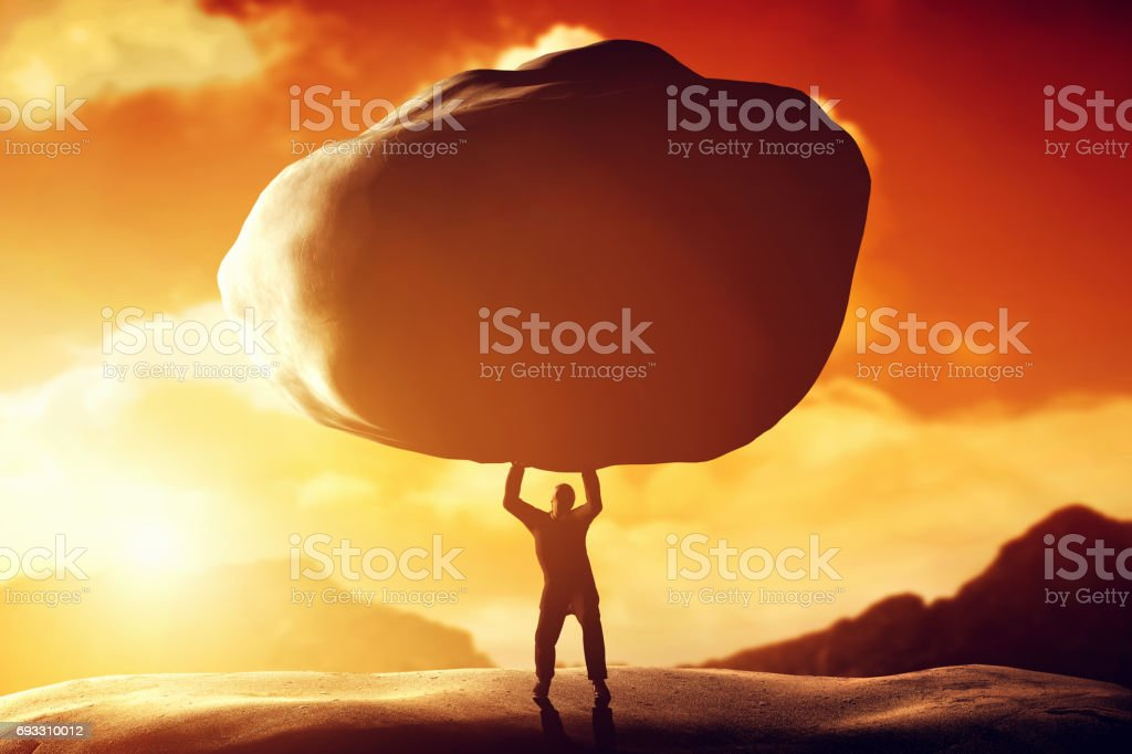 Man lifting a huge rock. Concept of strength, ballast, difficulty, power stock photo