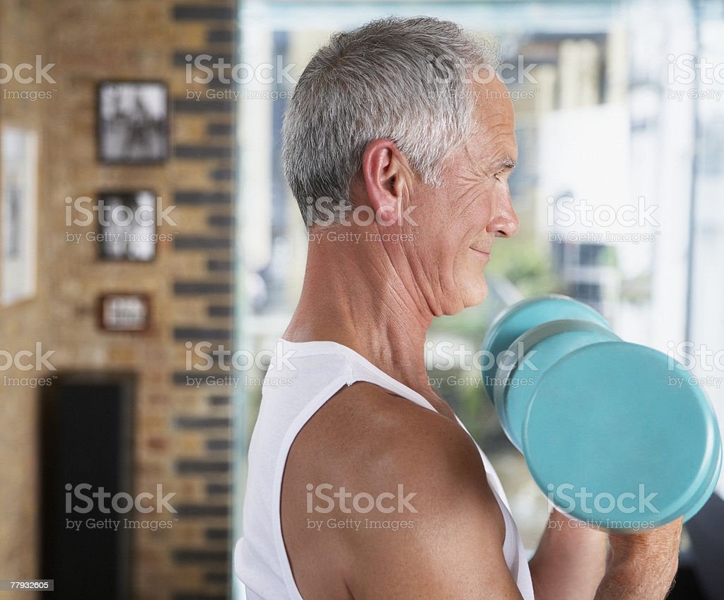 Man lifting dumbbells in living room royalty-free stock photo