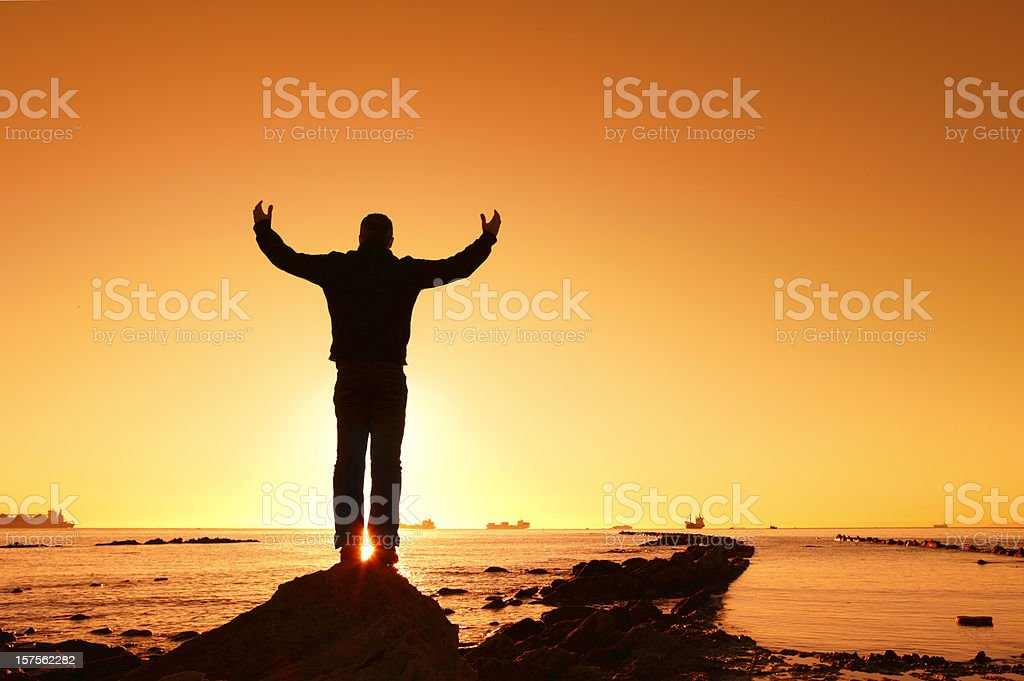 Man Lifting Hands at Sunrise stock photo
