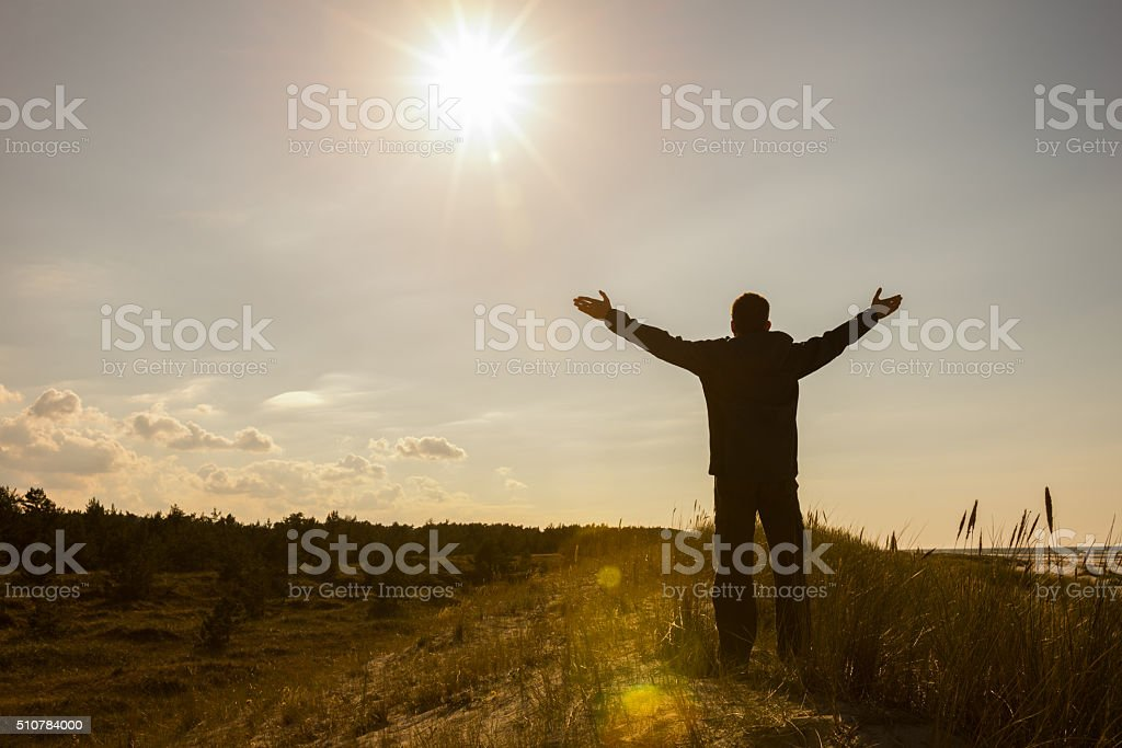 Man lifting his hands up silhouette background stock photo