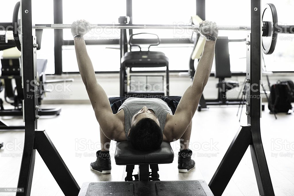 Man lifting weights on weight bench stock photo