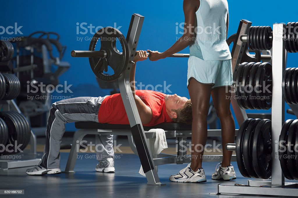 Man lifting weights with a spotter stock photo