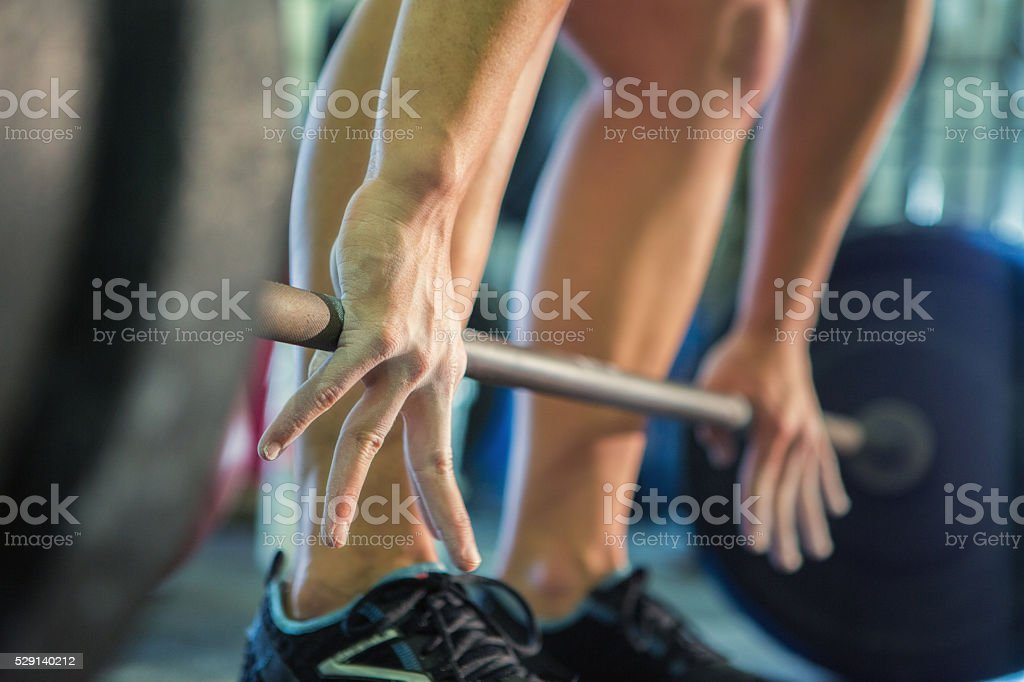 Man lifts barbell weights in gym stock photo