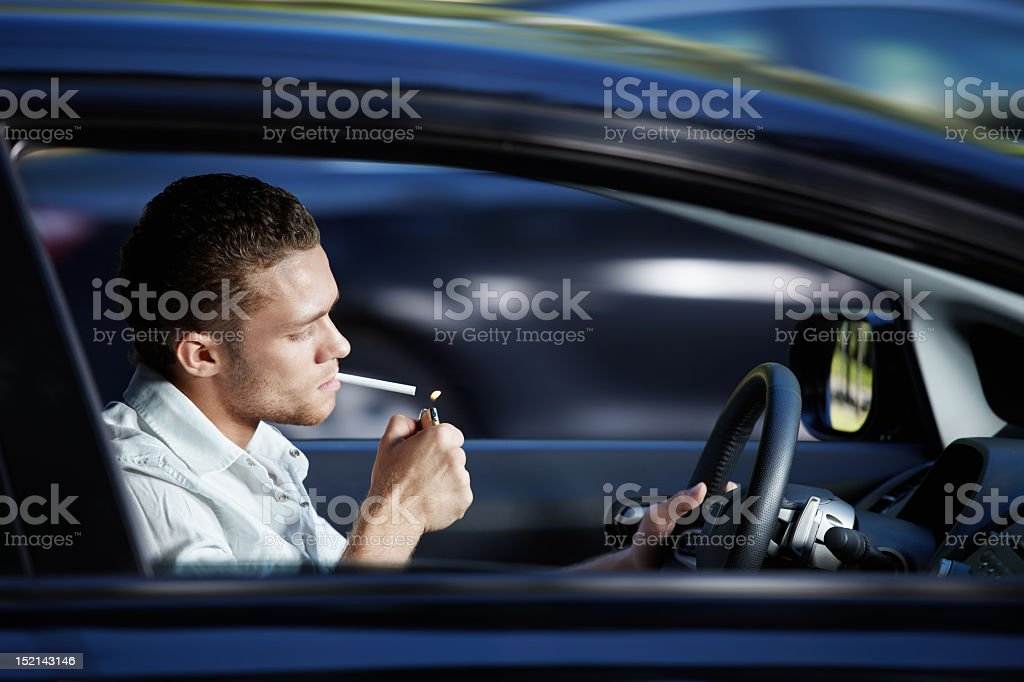 A man lighting a cigarette while driving a car royalty-free stock photo