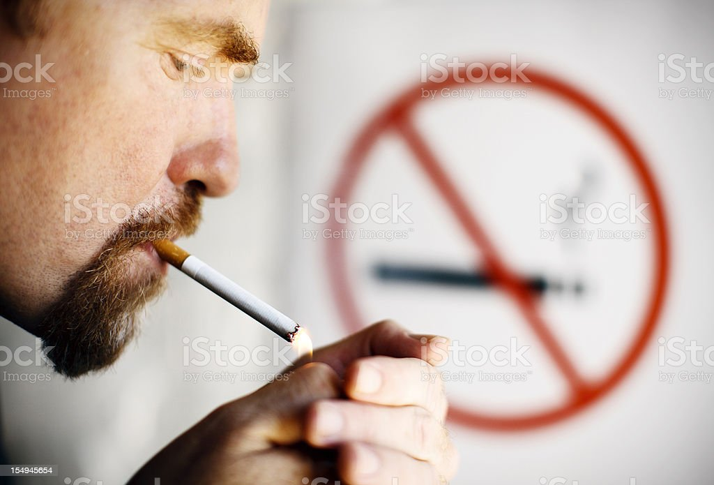 Man lighting cigarette in front of No Smoking sign royalty-free stock photo