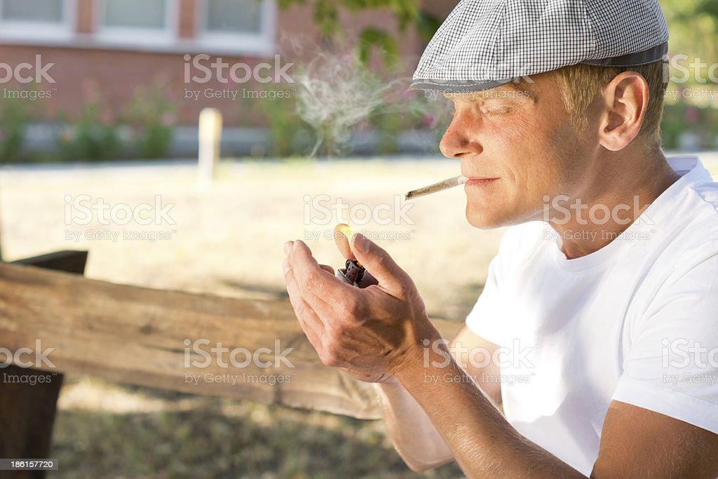 Man lighting up a cannabis joint royalty-free stock photo
