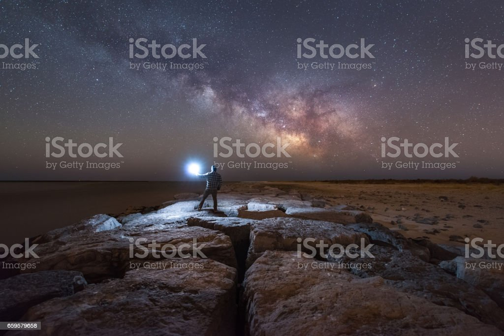 Man lighting up a jetty under the milky way galaxy stock photo