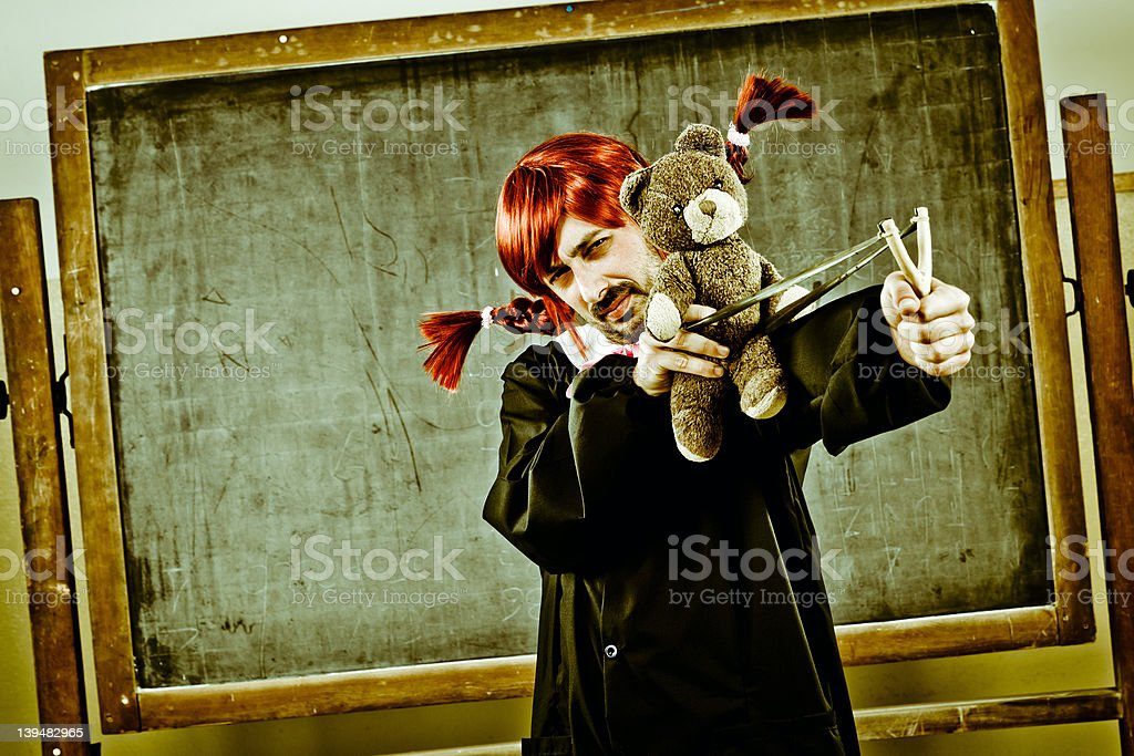 Man like Schoolgirl is shooting a Teddy Bear. Humor stock photo