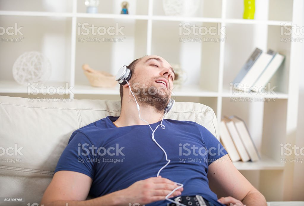 Man listening music in headphone on the sofa at home, stock photo