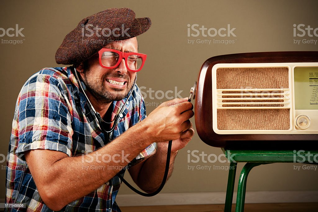 Man listening to an old radio with stethoscope royalty-free stock photo