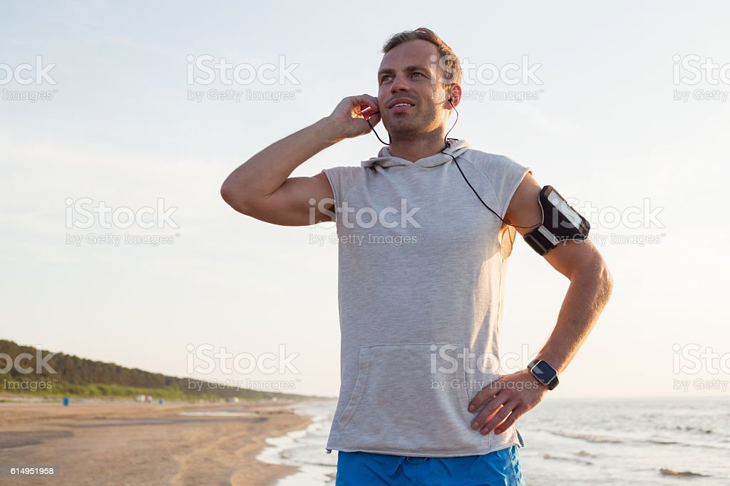 Man listening to music while working out on the beach stock photo