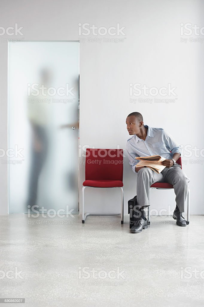 Man Listening To People Talk Behind Translucent Door stock photo