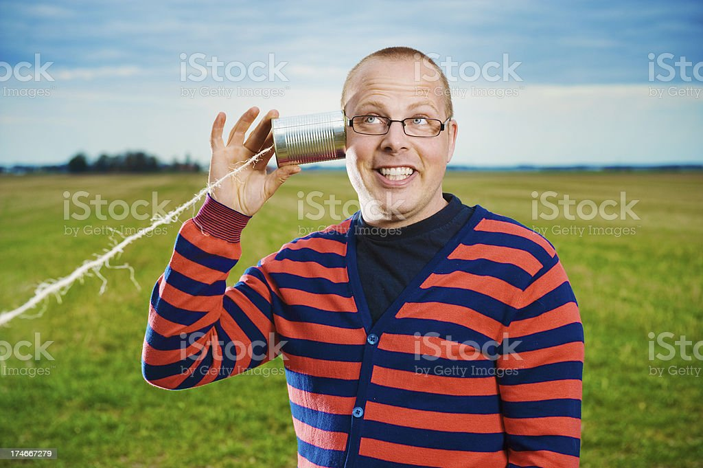 Man listening to something in his tin can phone royalty-free stock photo