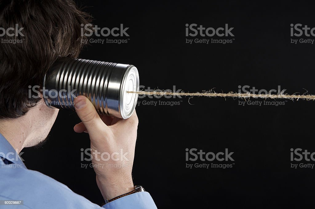 Man listening to tin can telephone stock photo