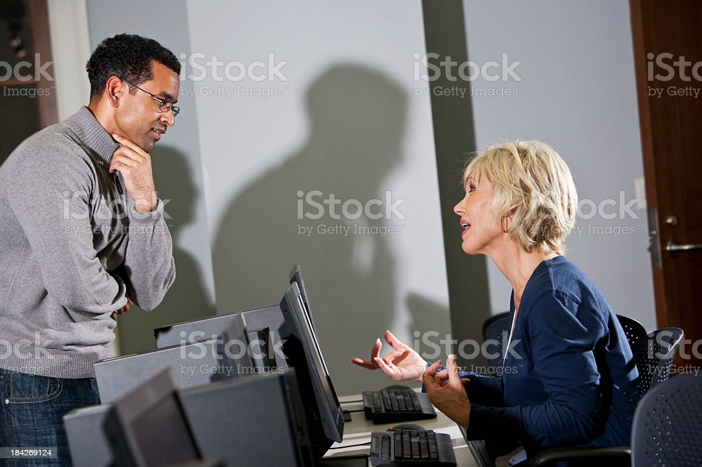 Man listening to woman using computer stock photo