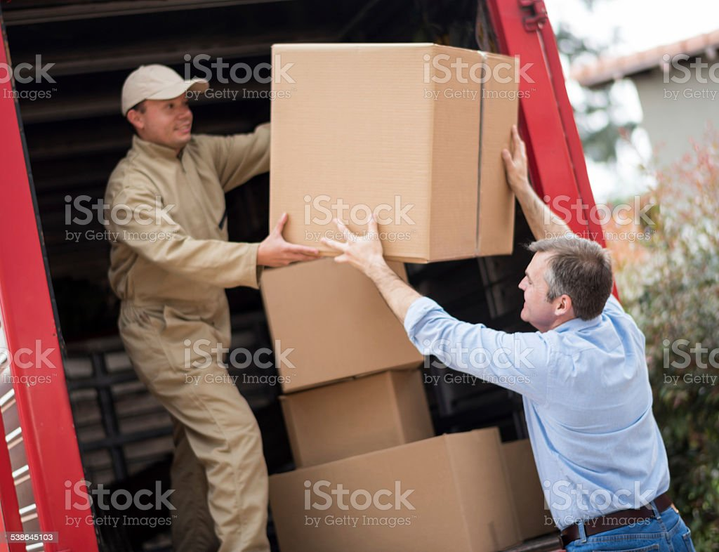 Man loading a moving truck with movers stock photo