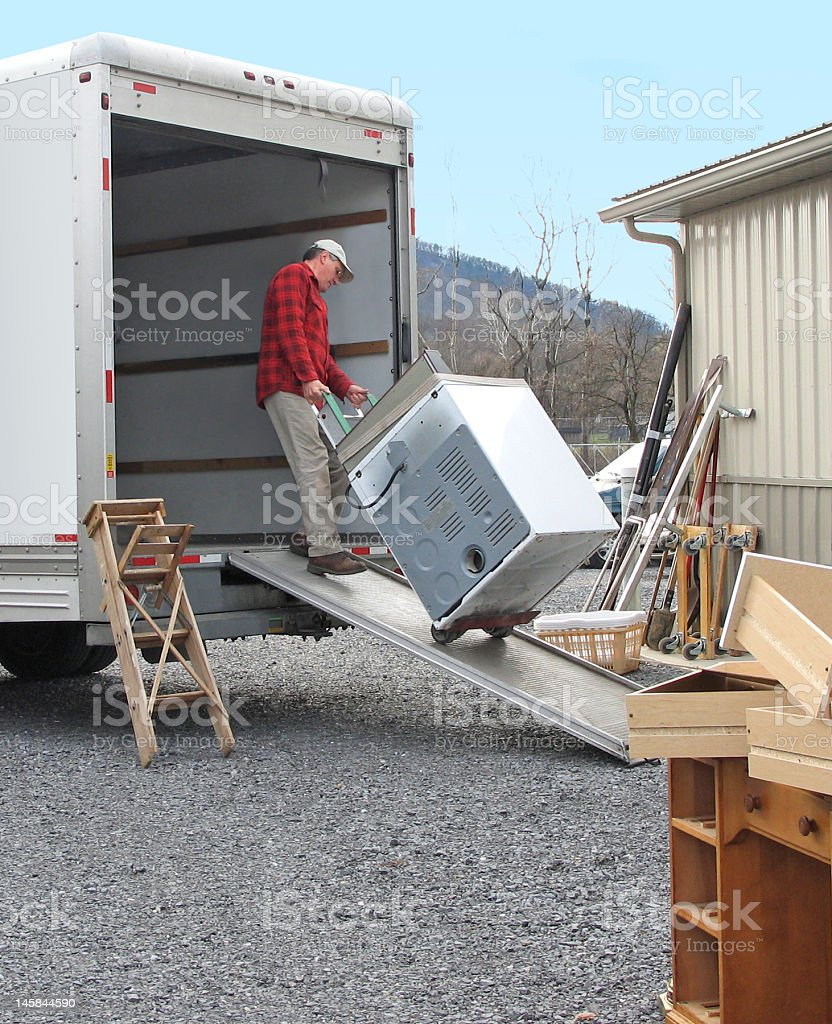 A man loading a moving van with a washer stock photo