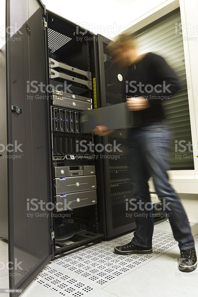 Man loading components into a server rack stock photo