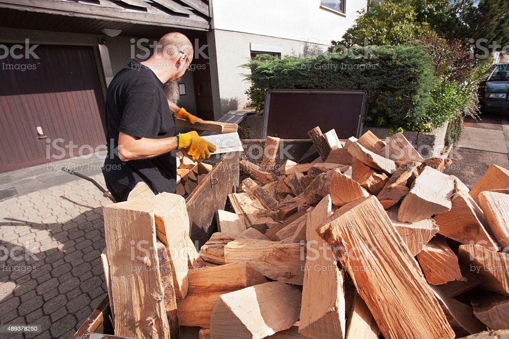 Man loading hand wagon with firewood stock photo
