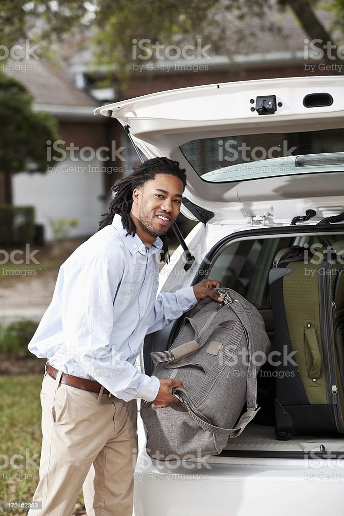 Man loading suitcase in car stock photo