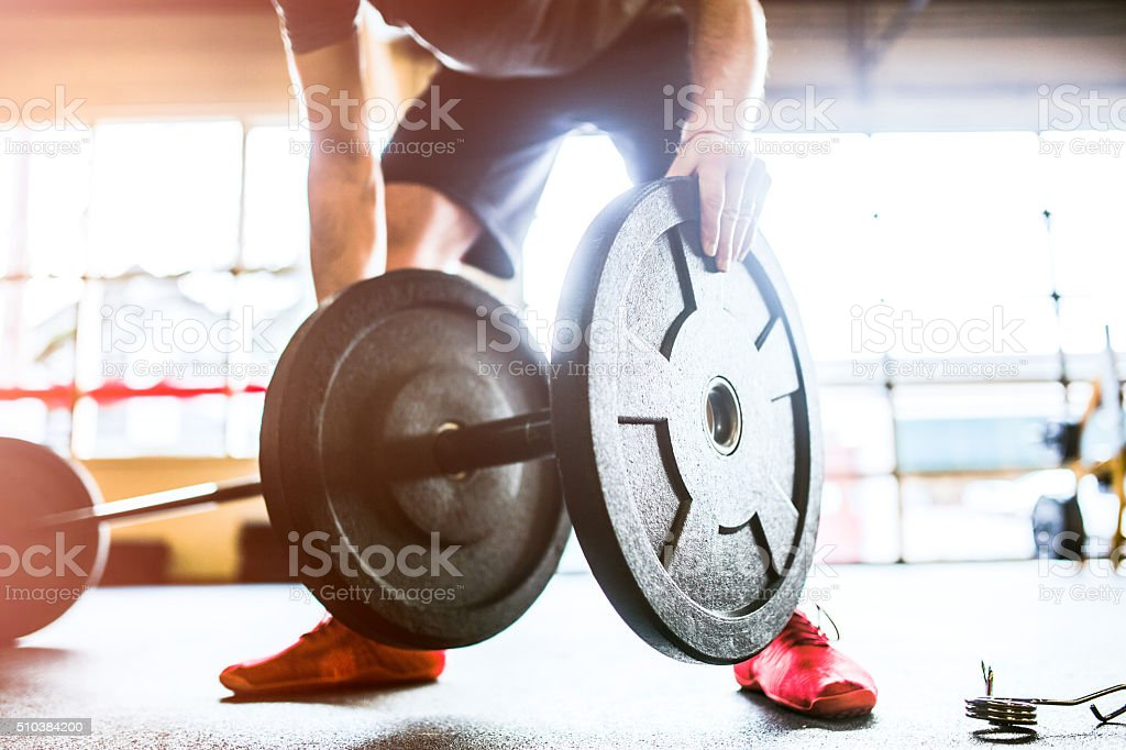 Man Loading Weights to Barbell stock photo