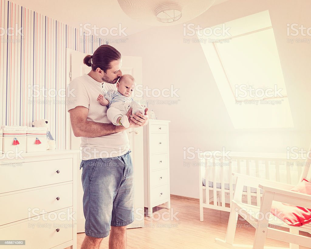 Man looking after baby boy, holding son on hands, retro stock photo